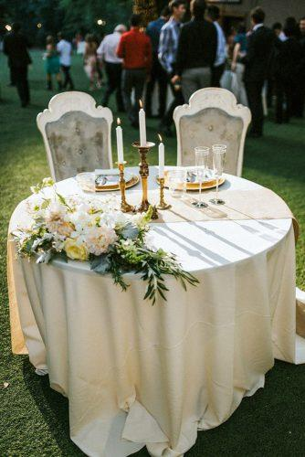 rustic wedding reception round sweetheart table with vintage chairs and flowers seth & kaiti photography