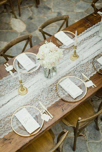rustic wedding reception simple wooden table decorated with lace with gold dishes jophoto