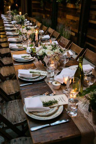 rustic wedding reception table and chairs of dark wood on the table flowers and candles greenery nyc