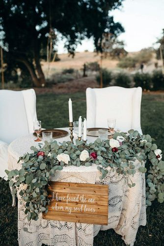 rustic wedding reception table of the bride and groom covered with white lace decorated with greenery and flowers wooden sign board the family films