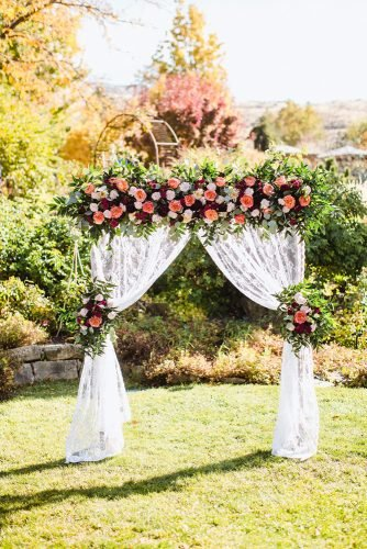 rustic wedding reception white lace arch with bright roses and greenery radionphotography