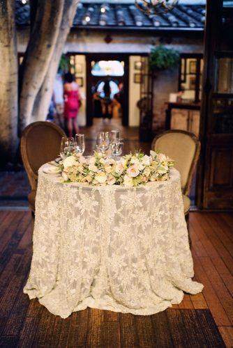 rustic wedding reception white lace tablecloth in italian style with white roses joyeusephotography
