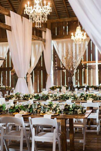 rustic wedding reception with greenery on wooden table elegant chenderliers in the barn ashley giffin photography