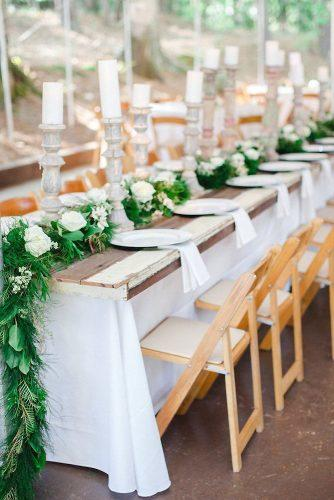 rustic wedding reception wooden board on the table and tall candres sawyer baird photography