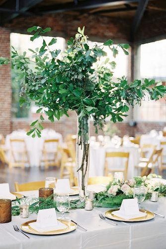 tall wedding centerpieces in a high glass vase twigs with leaves heather payne photography