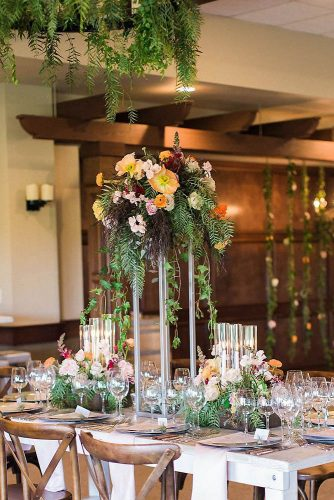 tall wedding centerpieces on a wooden table a minimalist stand with flowers and greens ashley bee via instagram