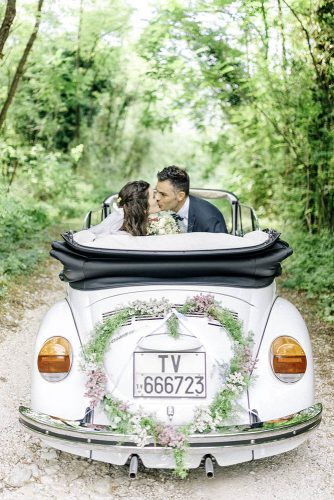 wedding car decorations the bride and groom kiss in a white convertible garnished with green and flowers in the shape of a heart sarah jane ethan photography