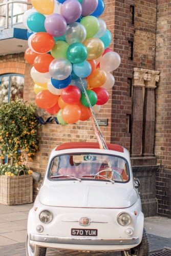 wedding car decorations with a huge armful of balloons holly clark photography