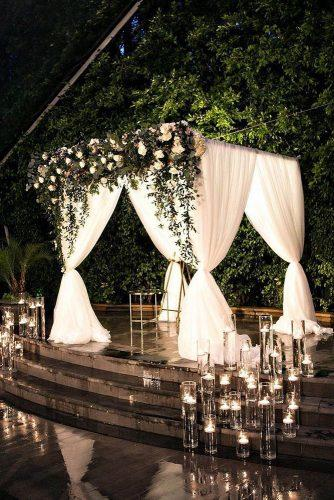 wedding ideas with candles bridal ceremony arch with white cloth greenery and white flowers lauriebaileyphoto