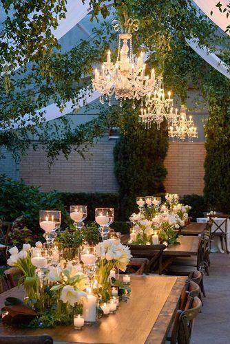 wedding ideas with candles on table reception under the tent with greenery and chandelier karlischstudio_weddings