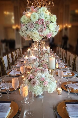 wedding ideas with candles tall centerpiece and candels in glass with pale pink roses and white flowers edgedesigngroup