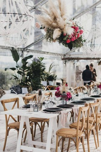 wedding reception decorations black and white with wooden chairs bright roses feathers under a transparent tent nina claire via instagram
