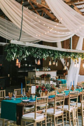 wedding reception decorations blue tablecloth and candles wooden boxes with flowers over the table beams with light bulbs and greens j a m i e m e r c u r i o via instagram