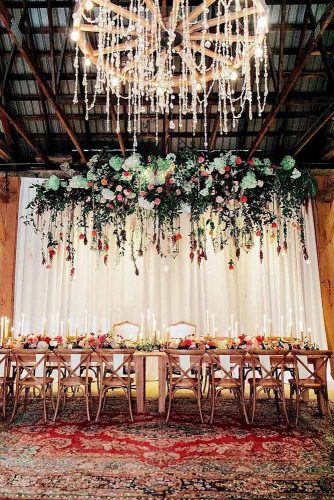 wedding reception decorations boho in barn luxurious chandelier long table with flowers scenery of flowers carpet with patterns on the floor serena jae via instagram