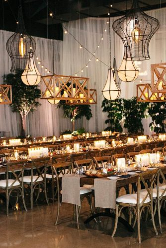 wedding reception decorations long wooden tables with candles over tables modern chandeliers and luminous garlands k y l e j o h n via instagram