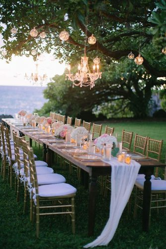 wedding reception decorations outdoor long wooden table with candles and flowers golden chairs over a table elegant chandelier and glowing balls dmitri & sandra via instagram
