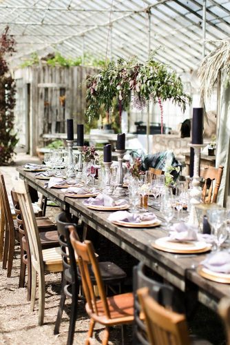 wedding reception decorations rustic wooden table and different chairs beautiful black candles bohemian dishes flowers and greens becky davis photography via instagram