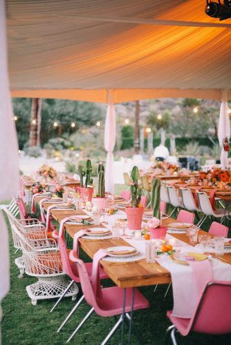 wedding reception decorations under a white awning light brown wooden table bright pink chairs and cacti on the table gideonphoto via instagram