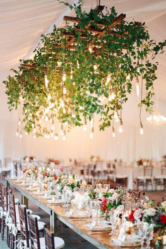 wedding tent long table with flowers under the awning above him greens and light bulbs almond leaf studios via instagram