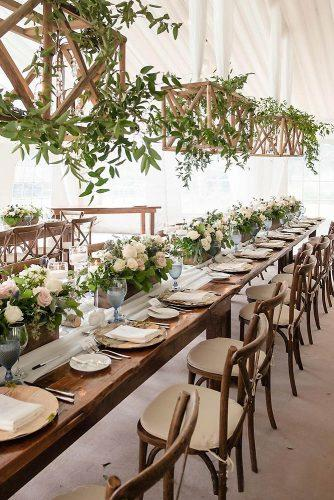 wedding tent reception in rustic style decorated with suspended wood and greenery rowellphoto via instagram