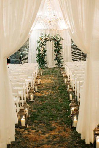 wedding tent romantic ceremony with lanterns candles aisle and greenery altar christinaloganevents