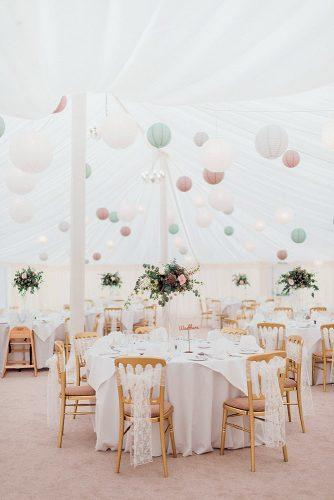 wedding tent round tables with white tablecloths and flowers under an awning decorated with pastel balls kathryn hopkins photography
