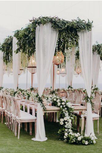 wedding tent white cloth and greenery with white roses tablerunner and hanging chandelier fontainephoto