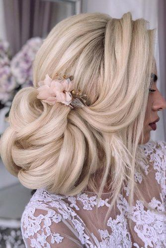 wedding updos for long hair volume side bun on blonde hair decorated with pink flower hairpin komarova_websalon