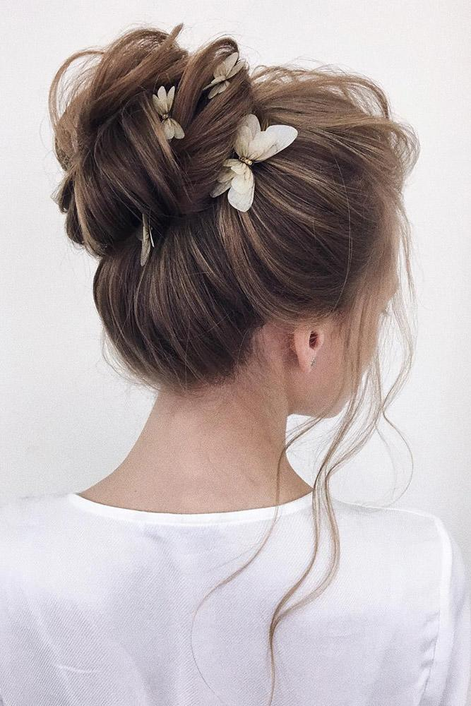 bridal hairstyles elegant airy high bun with butterfly pins xenia_stylist