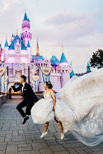 disney wedding funny couple jumping near disney castle