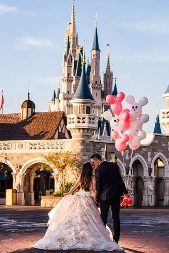 disney wedding newlyweds kissing near disney castle