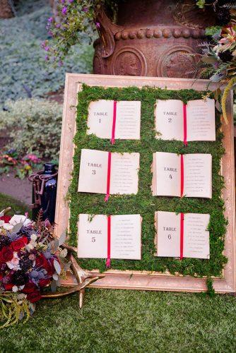 disney wedding table plan with moss and books from alise in wonderland raelyn elizabeth photography