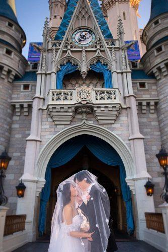 disney wedding the bride and groom under the veil on the background of the castle disney fine art photography
