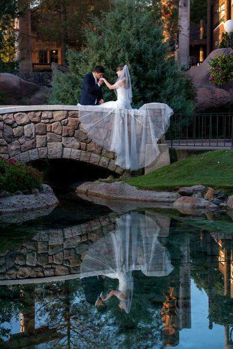 disney wedding the groom kisses the bride's hand on the bridge over the water disney fine art photography