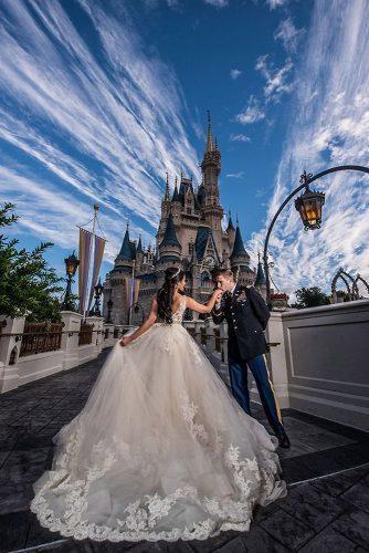 disney wedding the groom kisses the hand of the bride against the background of the castle disney fine art photography