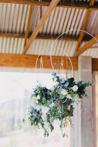 greenery wedding décor suspended metal rings decorated with a cascade of greenery and flowers vanilla photography