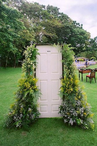 old door wedding decoration white door painted with bushy greens and flowers mark cantalejo photography