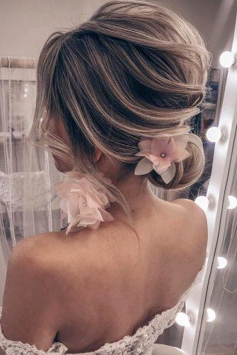 summer wedding hairstyles textured low bun on blonde hair with pink flowers tanya_ilyasevich