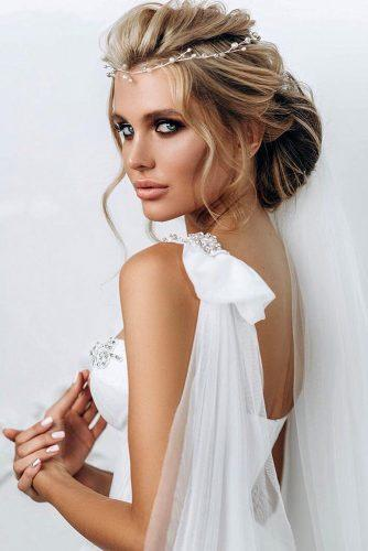 swept back wedding hairstyles low volume bun on blonde hair with silver halo muamatveyeva