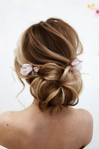 swept back wedding hairstyles volume low bun textured swept pink gentle flowers accessory nina.hair.stylist