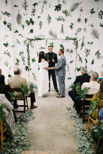 wedding altar decoration aisle and white walls decorated with different green leaves a wooden arch with greens and flowers the kama photography via instagram