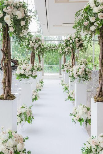 wedding altar decoration aisle decorated with tall trees and white roses bridal arch astin hwang via instagram