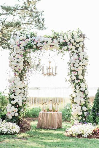 wedding altar decoration arch of white flowers with an altar and a golden chandelier with candles aj dunlap via instagram