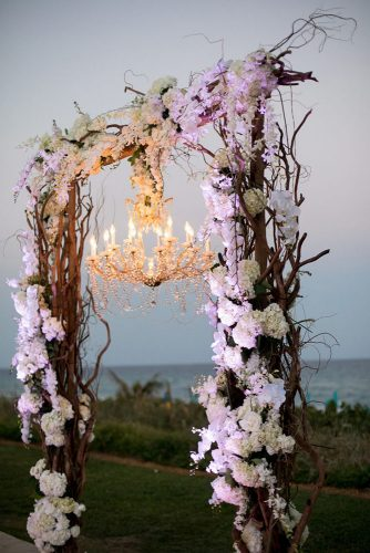 wedding altar decoration arch with wooden branches orchid flowers with elegant chandelier sara kauss photography via instagram