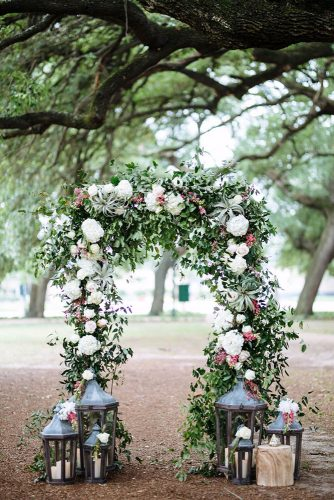 wedding altar decoration in the rustic style of greenery and white flowers decorated with lanterns with candles becki___smithhousephoto via instagram