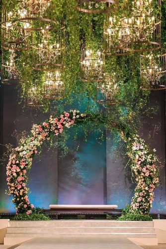 wedding altar decoration on a cosmic background a round floral arch decorated with green and ruddy flowers under the ceiling greens and chandeliers the white boutique via instagram