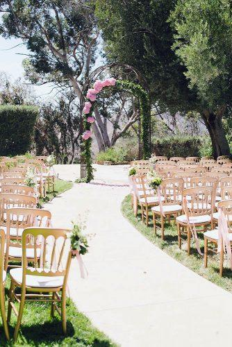 wedding altar decoration pink metal arbor with an arch of greenery and pink flowers onelove photography