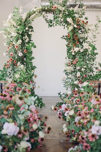 wedding altar decoration the arch and a passage are decorated with greenery and field flowers nicole land via instagram
