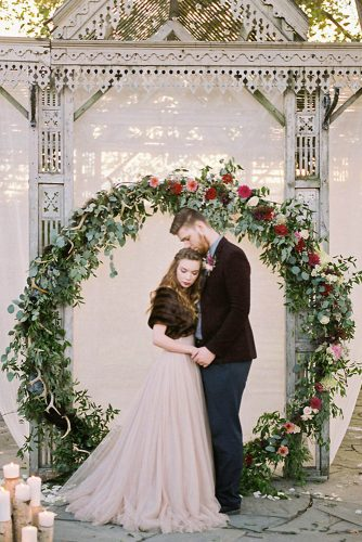 wedding altar decoration the bride and groom embrace against the background of a circular arch of greenery and flowers sophie kawalek