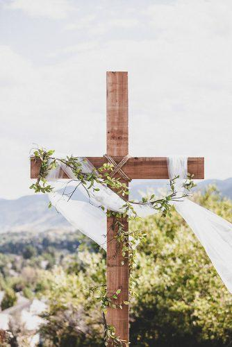 wedding altar decoration the wooden cross is decorated with green and light white cloth alicia gines photography